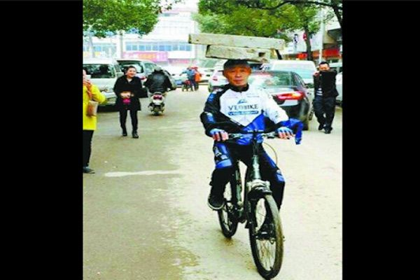 50 years old man rides bicycle with 74 kg stone on head