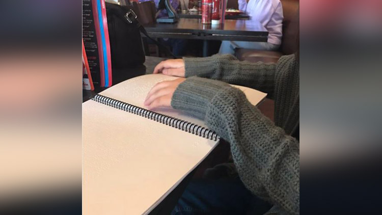 visually impaired girl reads a menu card for the first time