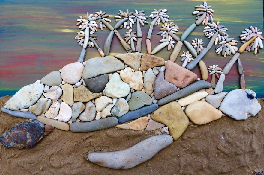 artwork made of stones coming out of the sea