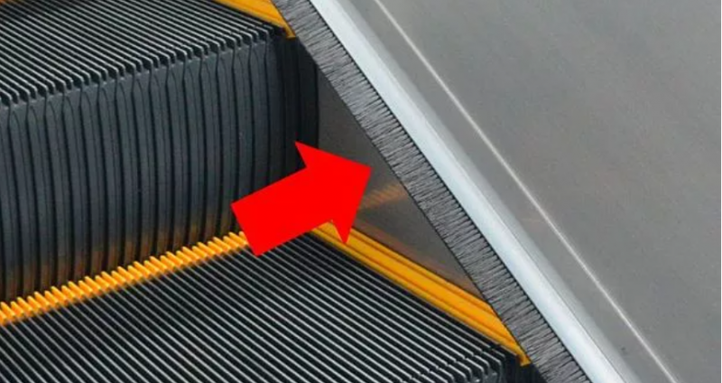Why do escalators have brushes at the bottom of the side
