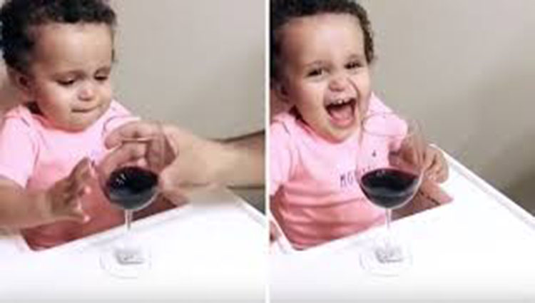 dad gives baby girl a glass of wine for drink