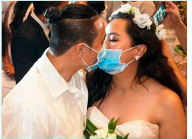 Newlyweds kiss through coronavirus masks in Philippines