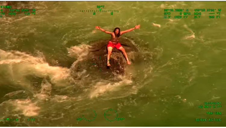 man trapped on rock in raging waters rescued