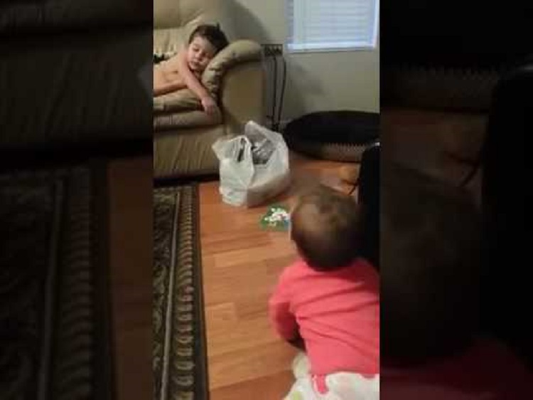 Baby sister tries to wake her big brother
