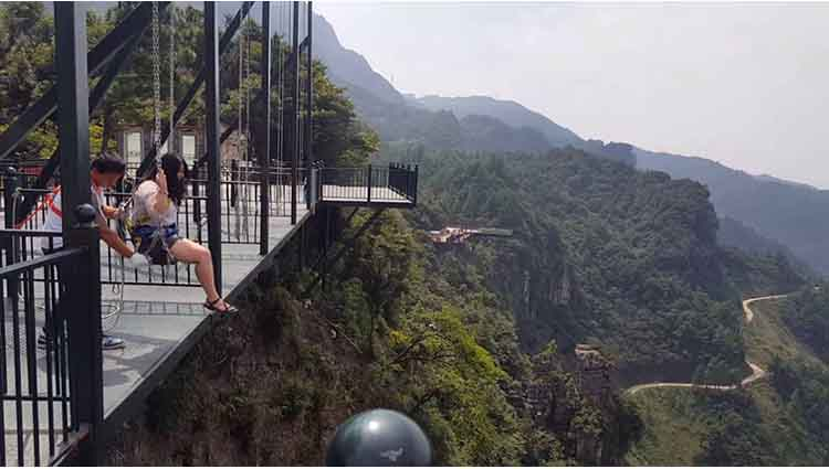 Thrill-seeker rides a swing on the edge of a 1,000-foot-tall cliff in China Chongqing